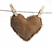 Valentine linen Sackcloth heart held by clothespins isolated on white
