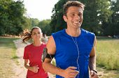 Young Man Listening To Music While Jogging With Woman