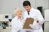 Male and female technicians writing on a clipboard in medical laboratory