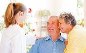 pic of geriatric  - Happy elderly couple talking with their carer - JPG