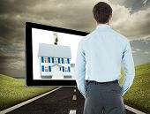 Businessman standing with hands in pockets against highway under cloudy sky