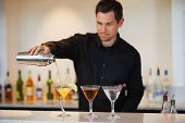 foto of bartender  - Bartender pouring cocktails at the bar - JPG
