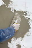 stock photo of insulator  - Worker spreading mortar over styrofoam insulation with trowel - JPG