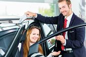 Seller or car salesman and female client or customer in car dealership presenting the interior decoration of new and used cars in the showroom and hands over the car keys