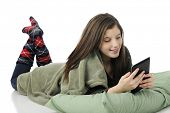 A pretty young teen playing on her iPad while laying on her belly with a pillow and blanket.  On a w