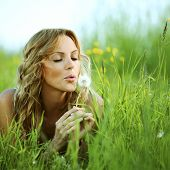 Young woman makes a wish blowing on dandelion