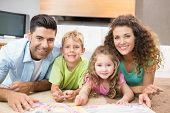 stock photo of storybook  - Happy siblings lying on the rug reading storybook with their parents at home in living room - JPG