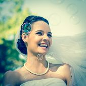 Close-up of a young beautiful bride looking at soap bubbles in the park