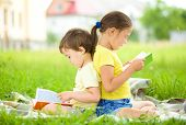 Little girl and boy are reading book while sitting on green grass