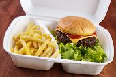 stock photo of burger  - Burger and fries portion in takeout food box - JPG