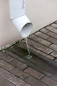 picture of downspouts  - Rain water flowing from a metal drain pipe - JPG