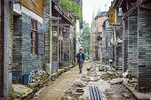 XINGPING, CHINA - MAY 28, 2014: A man strolls down a street in Xingping village. The village was ori