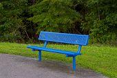 a metallic park bench on an overcast day