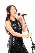 Elegant female singer singing on microphone isolated on white background