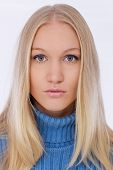 Closeup portrait of attractive young blonde woman with blue eyes, looking at camera.