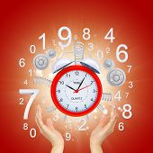 Hands hold alarm clock