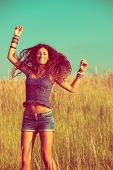 smiling young woman with long curly hair jump  in yellow summer grass, wearing jeans shorts and boho style top, retro colors
