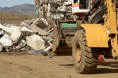 image of wheel loader  - Wheel loader being used to pile scrap metal at a metal recycling plant - JPG