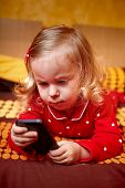 Girl Toddler Laying In Bed And Holding A Smartphone
