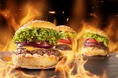 Delicious hamburgers with burning flames on background