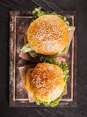 Delicious hamburgers served on black stone, shot from upper view