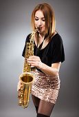 picture of saxophone player  - Beautiful blond woman saxophone player studio closeup shot - JPG