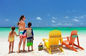 Family of mother and kids enjoying vacation at tropical beach with two colorful adirondack wooden chairs on white sand and turquoise ocean water in Caribbean