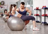 picture of crunch  - Personal trainer helping woman doing abs crunches with gym ball