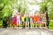Excited kids with arms and sit in row on bench