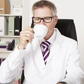 Male Doctor Drinking A Cup Of Tea Or Coffee