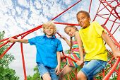 Two boys and girl sit on red ropes of playground