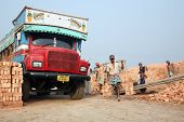 SARBERIA,INDIA, JANUARY 16: Brick field workers carrying complete finish brick from the kiln, and lo