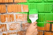 Human Hand With Green Colored Brush Painting Brick Wall
