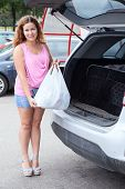 Attractive Young Woman In Pink Clothes Placing Bag In Suv