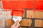 Paint Brush With Red Color On Brick Wall