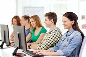 education, technology and school concept - smiling female student with classmates in computer class
