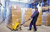 stock photo of pallet  - worker with fork pallet truck stacker in warehouse loading Group of cardboard boxes - JPG