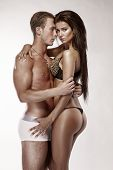 Sexy Couple, Beautiful Woman Holding A Muscular Man Isolated On A White Background