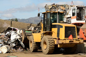 pic of scrap-iron  - Wheel loader being used to pile scrap metal at a metal recycling plant - JPG