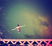 a boy jumping of an old train trestle bridge into a river toned with a retro vintage instagram filter effect