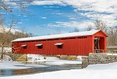 stock photo of covered bridge  - The red Cataract Falls Covered Bridge in rural Indiana crosses Mill Creek in a snowy winter landscape with a cloudy blue sky - JPG