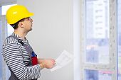 Foreman with construction plan in new building interior