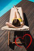 Beautiful woman in bikini relaxing by pool against heart
