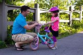 Father Teaching Daughter How To Ride A Bike