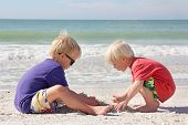 Two Young Children Playing In Sand On Beach By Ocean