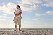Young Child Resting In Father's Arms On Beach By Ocean
