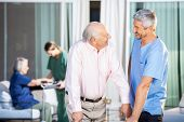 stock photo of male nurses  - Happy male caretaker looking at disabled senior man at nursing home yard - JPG