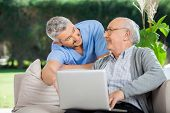 Smiling male nurse assisting senior man in using laptop at nursing home porch
