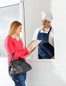 Happy woman purchasing uncooked ravioli pasta packet from chef through window