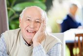 Portrait of happy senior man sitting at nursing home with grandson in background